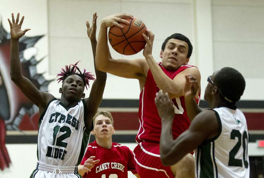 Caney Creek's Jeremiah Morales (20) grabs a rebound over Cypress Ridge's Devante Jenkins (12) and Josh Joubert (20) during the first quarter of a non-district high school basketball game at the New Caney ISD Tournament Thursday, Nov. 17, 2016, in Porter. Cypress Ridge defeated Caney Creek 109-40. Photo: Jason Fochtman/Houston Chronicle