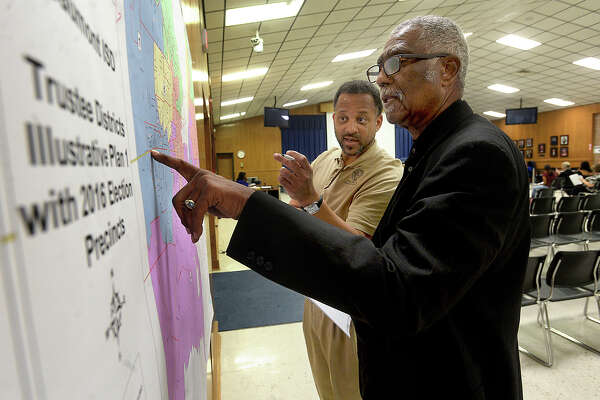 Rev. Oveal Walker, III, and Jefferson County employee Shedrick Evans discuss the map showing Beaumont Independent School District's proposed redistricting plan, which hung on the back wall of the meeting room during Thursday night's school board meeting. Among the agenda items discussed and voted upon was the redistricting proposal. Photo taken Thursday, November 17, 2016 Kim Brent/The Enterprise