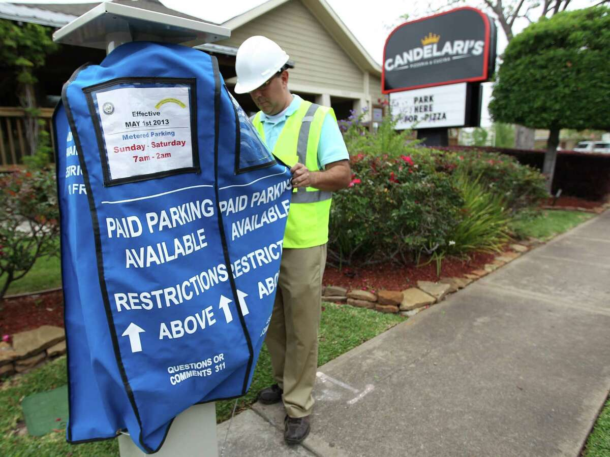 Andres Mesa places a cover over the newly installed parking meters along Washington Avenue on April 17, 2013.