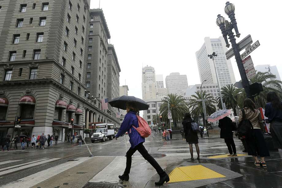 A woman carries an umbrella as she crosses Powell Street n San Francisco, Thursday, March 3, 2016. Bay Area residents can expect up to an inch of rain this weekend, forecasters said. Photo: Jeff Chiu, AP