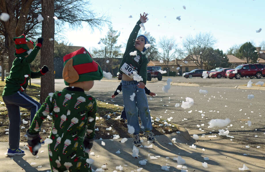 Brinnin Nethery, age 6, plays with foam snow during an Ugly Sweater 5K Run at the Museum of the Southwest. Photo: JAMES DURBIN
