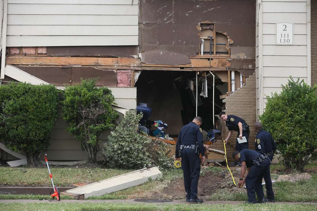 Police investigate the scene where a driver drove into an apartment at the intersection of Braes Forest Drive and Creekbend Drive, Friday, Nov. 18, 21016, in Houston. Officers said two children and two adults were home when the driver crashed through the wall. ( Jon Shapley / Houston Chronicle )