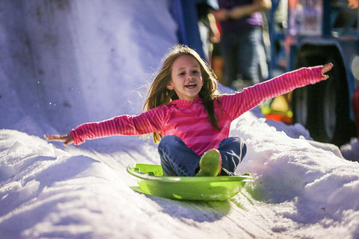 A girl sleds down a snowy hill at the Lighting of the Doves Festival and the International Winter On The Waterway hosted Sunday, Nov. 23, 2014, at Town Green Park.