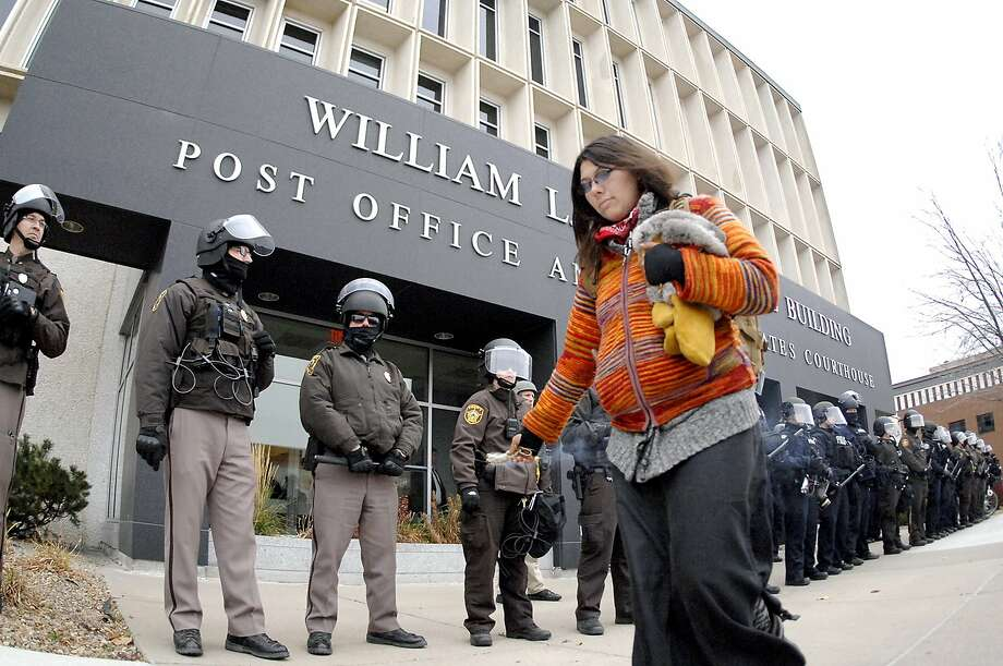 """An unidentified Dakota Access Pipeline protester leaves a trail of burning sage smoke as she walks past a row of law enforcement personnel standing guard in Bismarck, N.D. North Dakota on Thursday, Nov. 17, 2016. Ongoing protests of the four-state, $3.8 million pipeline in southern North Dakota have """"significantly strained"""" law enforcement and the state Highway Patrol, which provides security at the state Capitol, Republican House Majority Leader Al Carlson said. (Mike Mccleary/The Bismarck Tribune via AP) Photo: Mike Mccleary, Associated Press"""