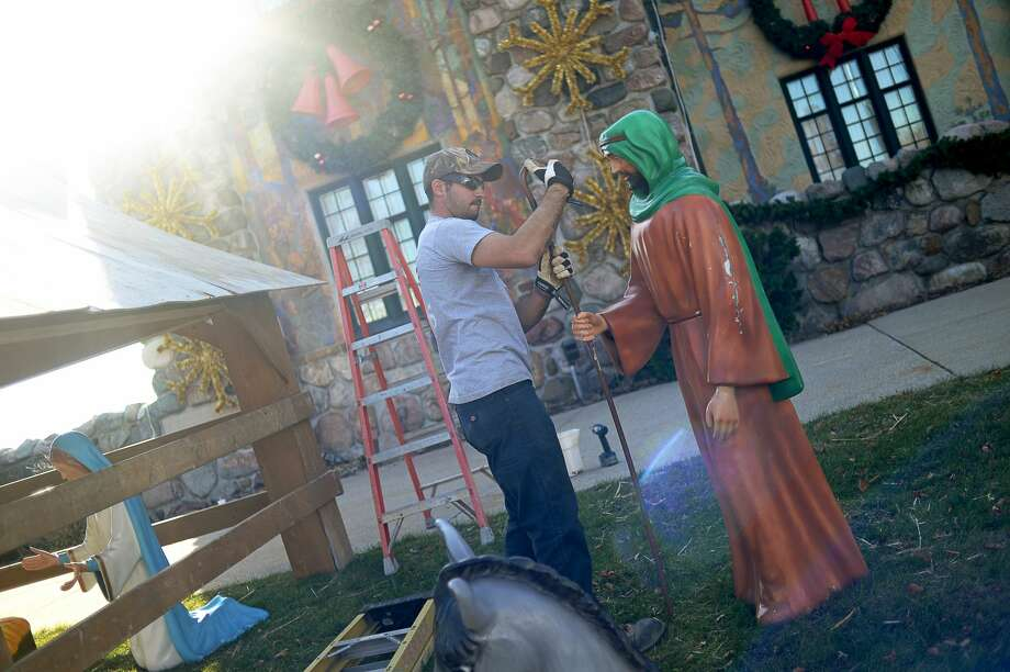 "Gerace Construction employee Brian Starks places a staff in the hands of a shepherd while setting up the Nativity in front of the Midland County Courthouse on Friday afternoon. Tomorrow, the Midland Santa Parade will begin at 10 a.m. near Midland High School and will wind its way to Main Street. This year's theme is ""Mistletoe Magic."" Photo: Erin Kirkland/Midland Daily News"