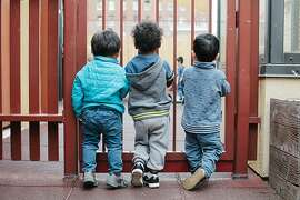 Mateo Xiu, William Rosales, and Eder Gongora Polanco, toddlers, stand on the roof looking in on the preschool children at Compass Children's Center in San Francisco, on November 15, 2016. The playground facility is divided into space for preschool children and toddlers.