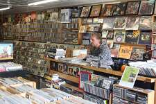 John Esposito of Disc & Dat record store in downtown Bethel, Conn., sorts through some new albums at his store in preparation for the post-Thanksgiving shopping weekend.