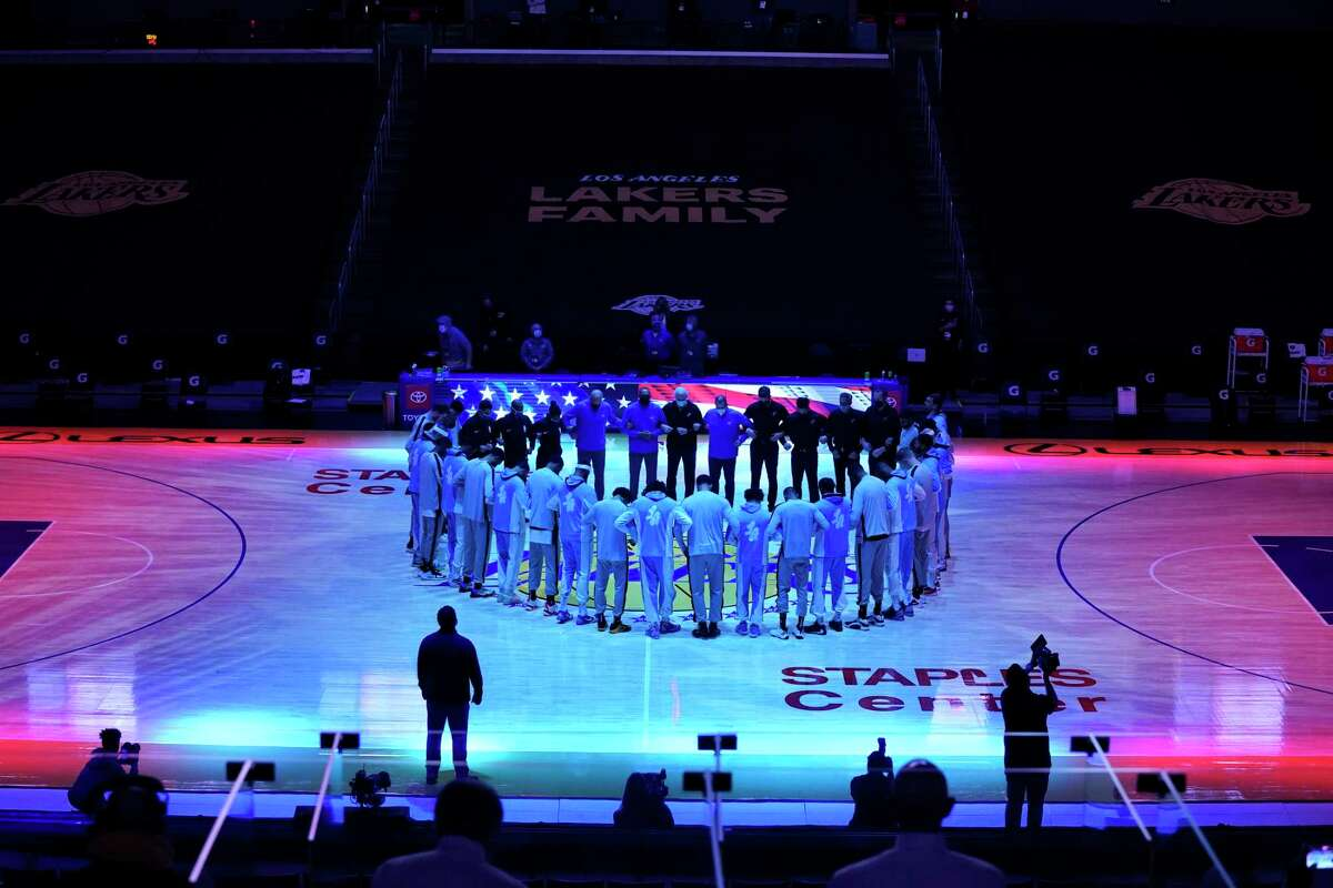 The San Antonio Spurs and the Los Angeles Lakers stand in a circle as the national anthem played before an NBA basketball game Thursday, Jan. 7, 2021, in Los Angeles. (AP Photo/Ashley Landis)