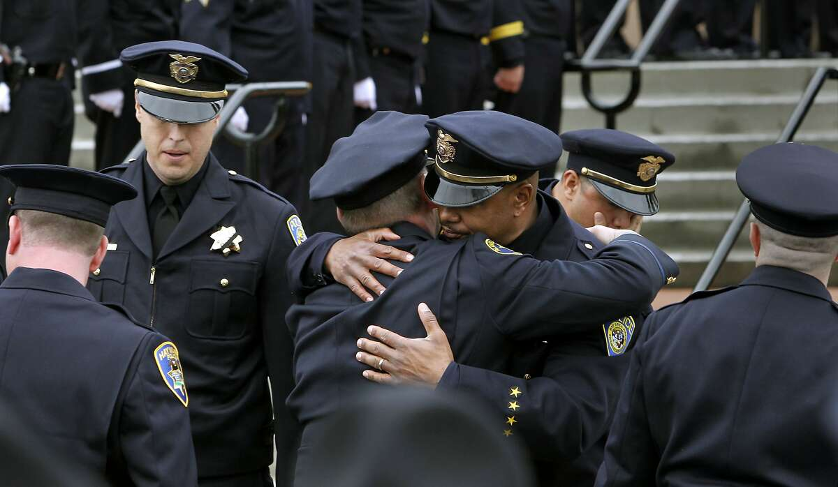 """Law enforcements officers console one another following the funeral service. BART police Sgt. Tom """"Tommy"""" Smith. Thousands of police, family and friends were in attendance at the neighborhood Church in Castro Valley, Calif. on Wednesday Jan. 29, 2013. Smith was shot and killed by a colleague during a probation search of an apartment in Dublin on Jan. 21."""
