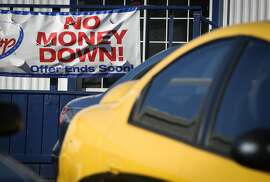 A sign advertises no money down at a used car dealership near Serramonte Blvd on Friday, November 18, 2016 in Daly City, Calif.