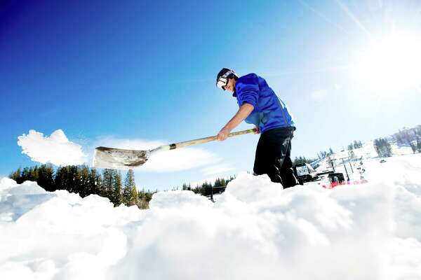 Ryan Warden shovels snow at Boreal Mountain Resort shortly before it opened for the season on Friday, Nov. 18, 2016, near Truckee, Calif.