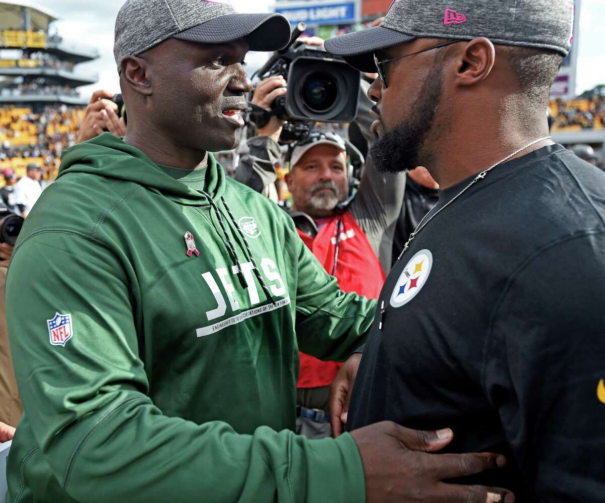 Pittsburgh Steelers head coach Mike Tomlin, right, and New York Jets head coach Todd Bowles visit following an NFL football game this season. The NFL has more steps in place than the NCAA to help advance minority coaches.