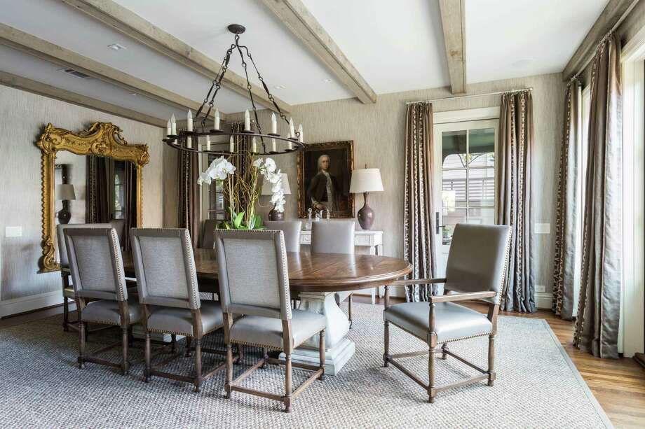Cathy Chapman created this dining room for restaurateur Tracy Vaught and chef Hugo Ortega. In this River Oaks home, elegant and rustic are combined for a dramatic effect with beautiful draperies and an elegant mirror. The table and chairs and broad chandelier are simpler but work well in the room. Photo: Julie Soefer / Julie Soefer Photography