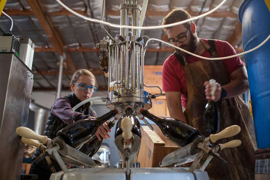 Winemaker Michael Cruse of Cruse Wine Co. and Ultramarine Wines readies to top off a bottle of sparkling wine after disgorging in in the blue barrel, as Erin Pooley corks the bottle at their warehouse winery in Petaluma, California, USA 17 Nov 2016. (Peter DaSilva/Special to The Chronicle) Photo: Peter DaSilva, Special To The Chronicle