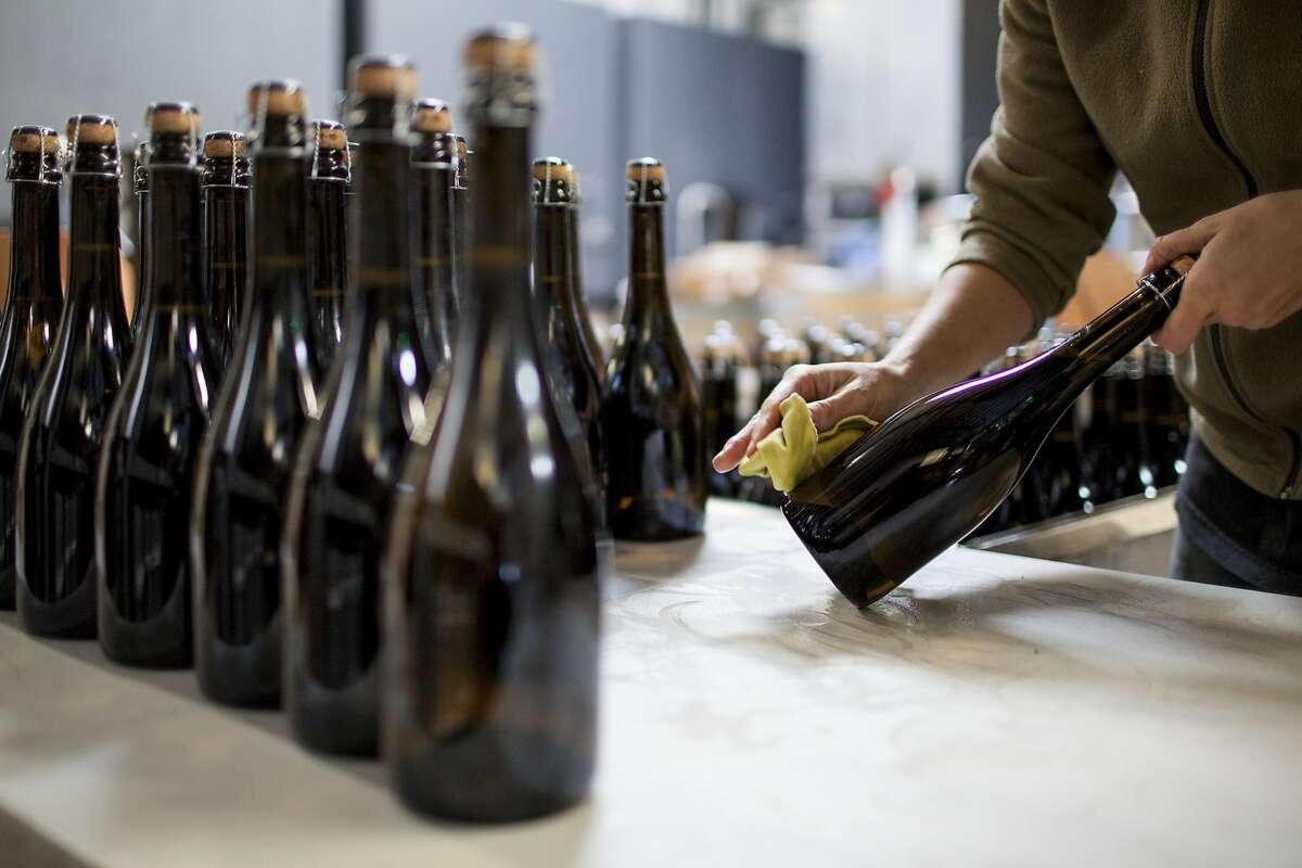 Krystal Goulart, wipes down freshly corked bottles of Ultramarine sparkling wine.