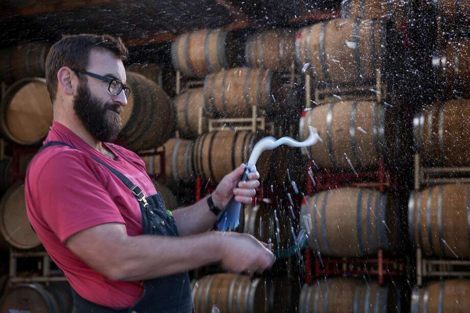 Michael Cruse disgorges a bottle of Ultramarine sparkling wine to remove the yeast sediment that has collected during aging. Photo: Peter DaSilva, Special To The Chronicle
