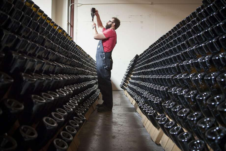 At his Petaluma winery, Michael Cruse inspects a bottle in the riddling racks. Photo: Peter DaSilva, Special To The Chronicle