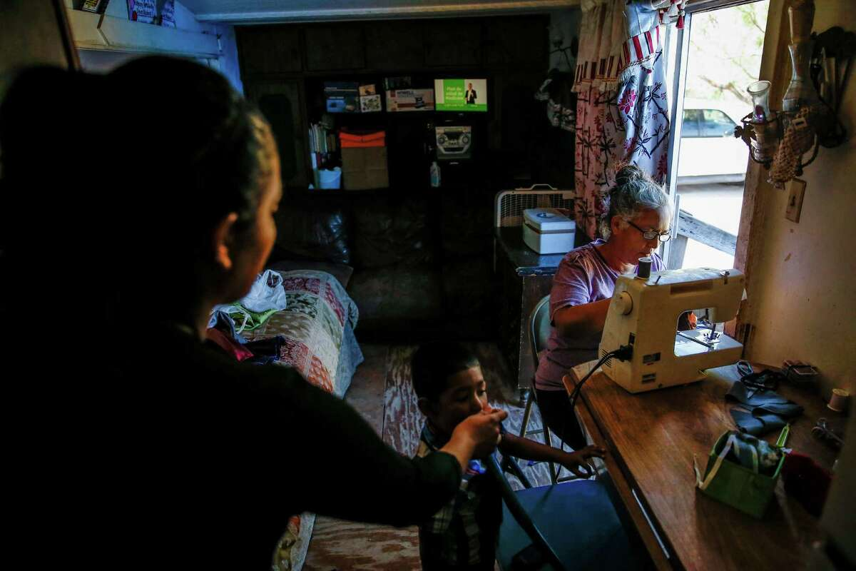 Rosi Maria Sanchez, right, makes clothes in her trailer in the Pueblo de Palmas colonia Tuesday, Nov. 15, 2016 in Penitas as her daughter, Yesenia Garibaldi, left, feeds her son. Sanchez and her daughters fled from their home in Mexico to escape cartel violence seven years ago. Since then, her husband has been deported after he was pulled over for running a red light and she now fears that a Donald Trump presidency means that they will be next.