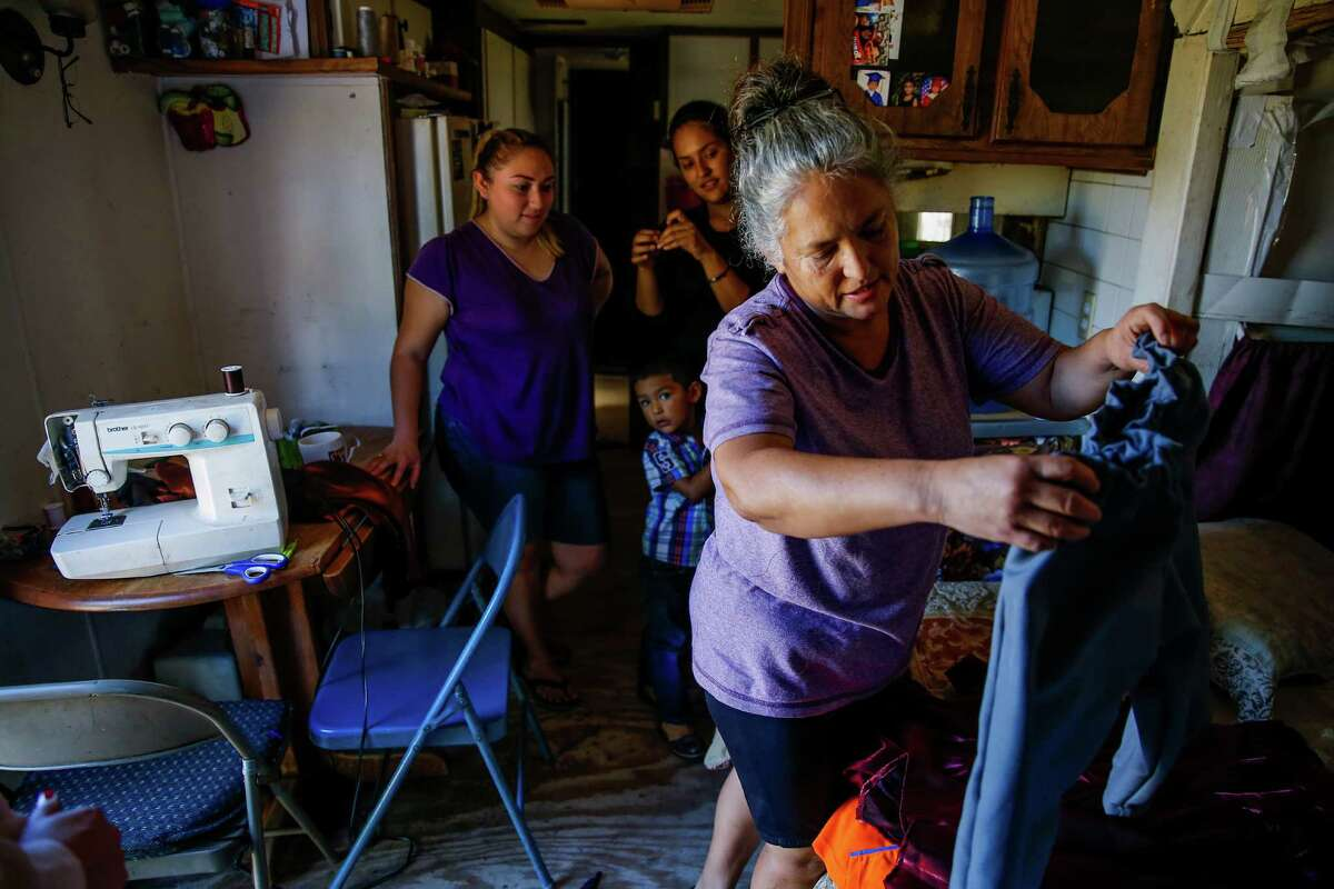 Rosi Maria Sanchez, right, folds clothes she made in her trailer in the Pueblo de Palmas colonia Tuesday, Nov. 15, 2016 in Penitas. Sanchez and her daughters fled from their home in Mexico to escape cartel violence seven years ago. Since then, her husband has been deported after he was pulled over for running a red light and she now fears that a Donald Trump presidency means that they will be next.