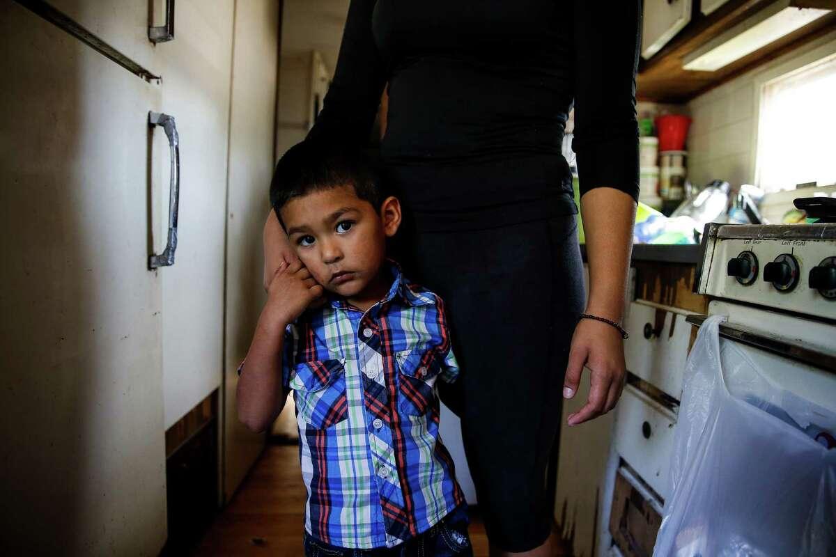 Kevin Garza Garibaldi, 2, hangs onto his mother, Yesenia Garibaldi, in his grandmothers trailer in the Pueblo de Palmas colonia Tuesday, Nov. 15, 2016 in Penitas.