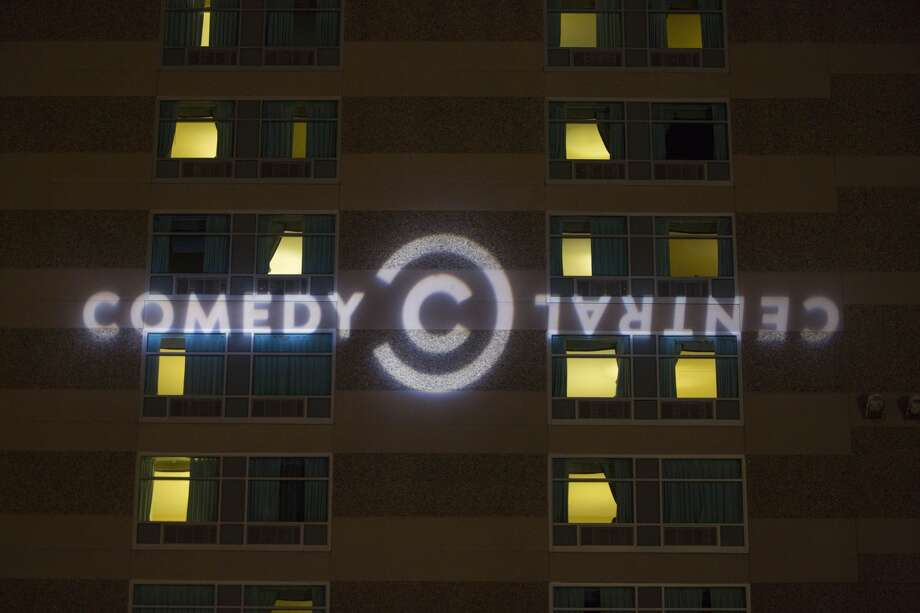 MANCHESTER, NH - FEBRUARY 05: The Comedy Central logo projected on the side of the Radisson Hotel before Comedy Central's 'The Daily Show with Trevor Noah' Presents 'Podium Pandemonium: A Debate About Debates,' New Hampshire Primary 2016 off-air event & post-reception on February 5, 2016 in Manchester, New Hampshire. Scroll ahead to see classic photos taken at the Chronicle Comedy Day in Golden Gate Park in 1987.