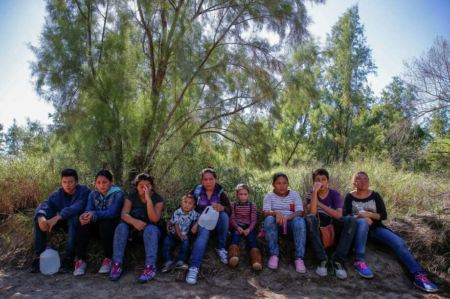 A group of immigrants sit next to a road after they crossed into the United States and were detained by Border Patrol Wednesday, Nov. 16, 2016 in McAllen. Most immigrants are arriving from El Salvador, Honduras and Guatemala where they are escaping violence and poverty. They hope to be found by border patrol to be processed, released and begin the process to stay in the country. Photo: Michael Ciaglo, Houston Chronicle / © 2016  Houston Chronicle