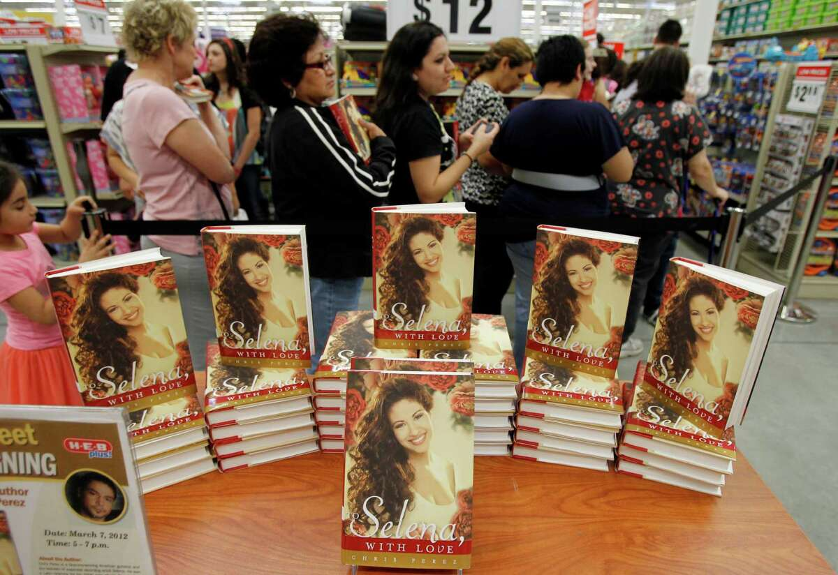 """Selena fans wait in line near stacks of the new book, """"To Selena, With Love,"""" Wednesday, March 7, 2012 before getting a chance to meet the author and Selena's former husband, Chris Perez, during an appearance at the H-E-B Plus in Corpus Christi, Texas. (AP Photo/Corpus Christi Caller-Times, Michael Zamora)"""