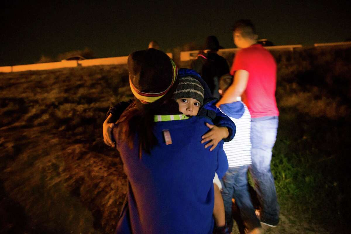 Luis Jafeth Duran, 3, looks over the shoulder of his mother, Jenny Marisa Rodriguez, as they seek out Hidalgo County constables to surrender themselves minutes after crossing the border at Anzalduas Park Tuesday, Nov. 15, 2016 in Mission. Rodriguez fled from Honduras after local gangs threatened to harm her son if she didn't give them information about her husband, who ran away when the gangs were pressuring him to join them. She hasn't heard from her husband in a year.