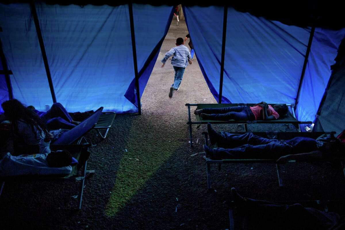 Kids run out of a temporary shelter as other immigrants, most of whom are escaping violence and poverty in El Salvador, Honduras and Guatemala, claim cots to spend the night at Sacred Heart Catholic Church Tuesday, Nov. 15, 2016 in McAllen. The church assists hundreds of immigrants everyday who arrive in McAllen after crossing the border by giving them food, clothing and a place to sleep if necessary.
