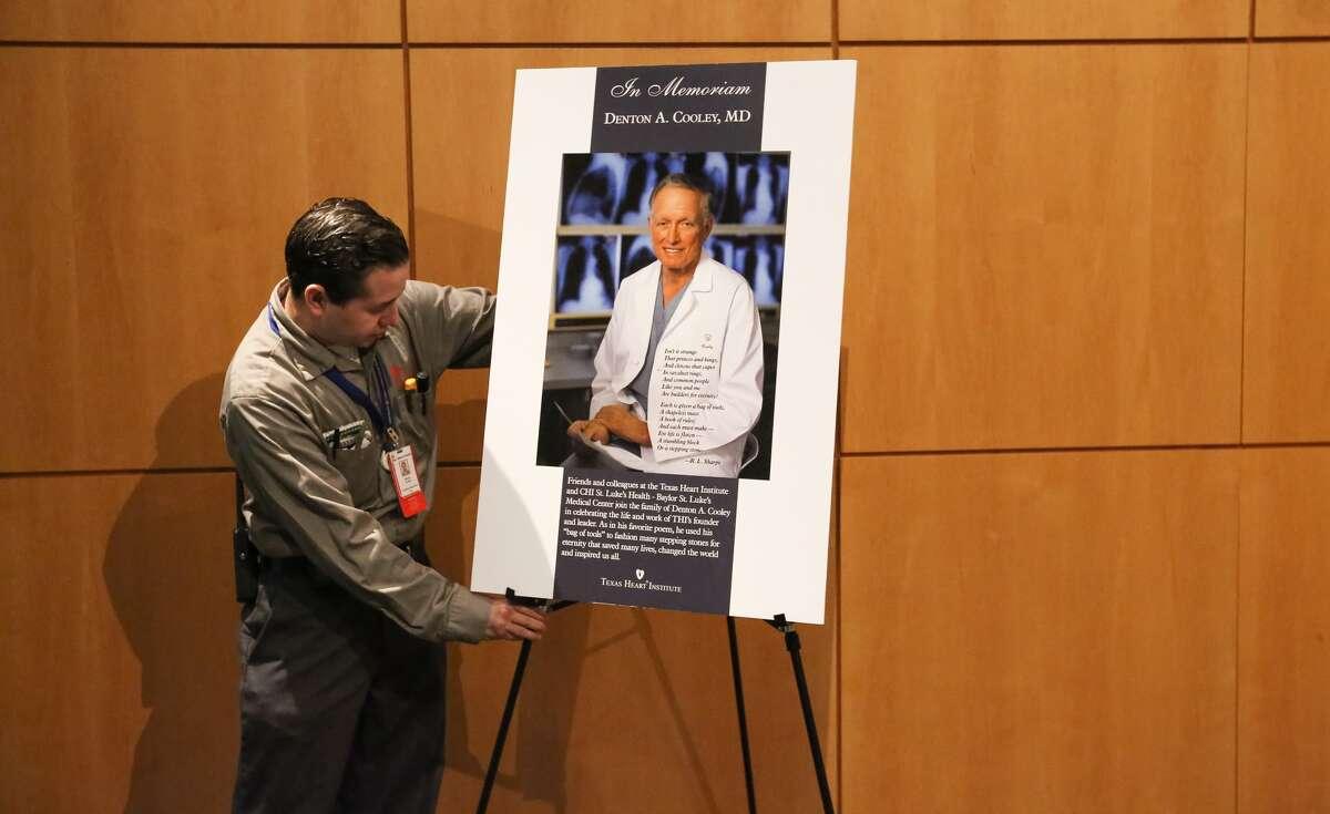 Alfonzo Huerta, a worker at Texas Children's Hospital, sets up a memorial poster of Dr. Denton A. Cooley at Texas Children's Heart Center on Friday.