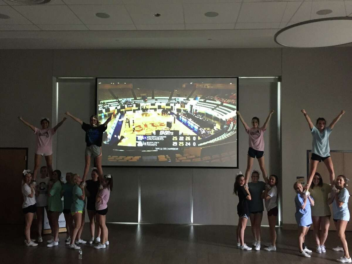 The Concordia Lutheran cheerleading squad hypes up the watch party at Concordia Lutheran High School Friday. The student body and teachers gathered to watch the state title match on the big screen, rewarded with an intense, hard-fought victory from their Lady Crusaders.