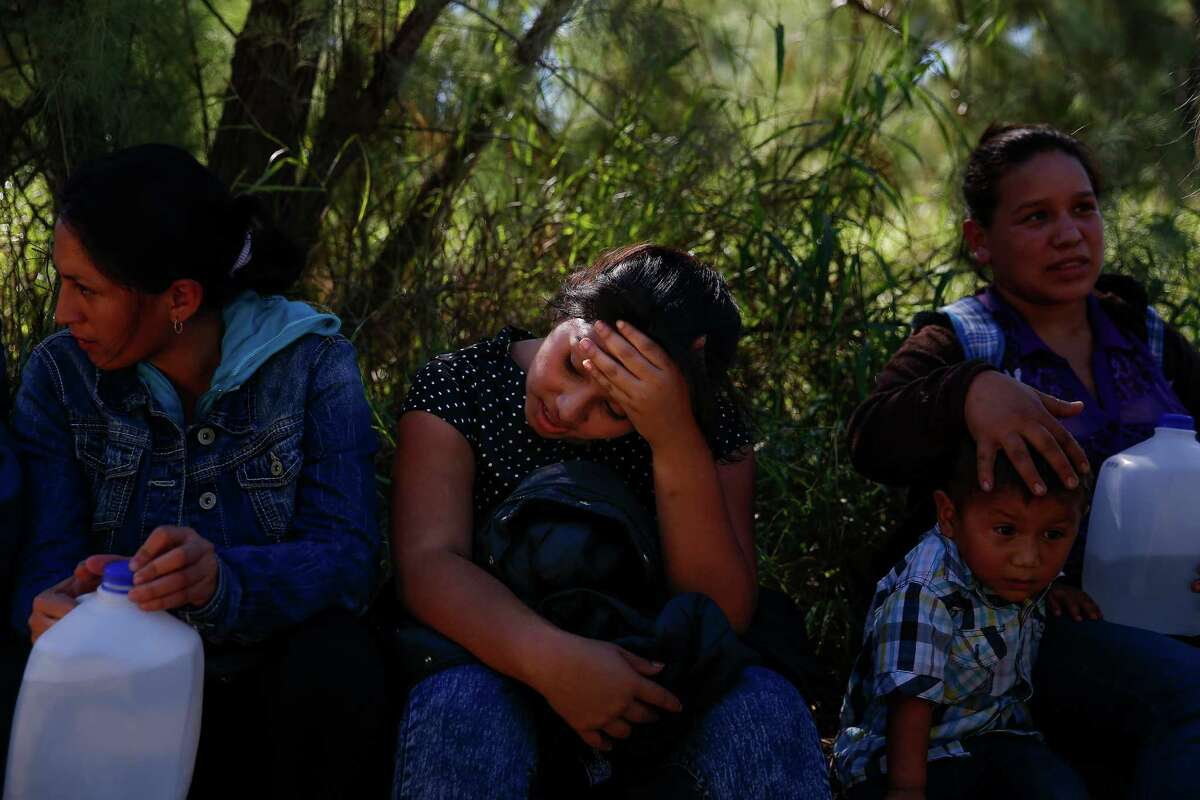 A young woman holds her head in her hand after she crossed into the United States Wednesday, Nov. 16, 2016 in McAllen. Most immigrants are arriving from El Salvador, Honduras and Guatemala where they are escaping violence and poverty. They hope to be found by border patrol to be processed, released and begin the process to stay in the country.