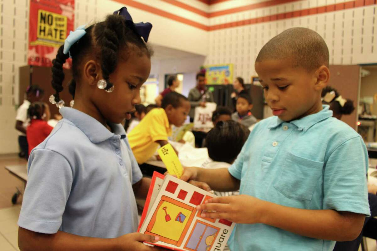 Thompson Elementary School first-grade students Kiya Taylor, left, and Ray Andrews look at one of the books donated by Half Price Books to the schoolÂ?'s literacy event.