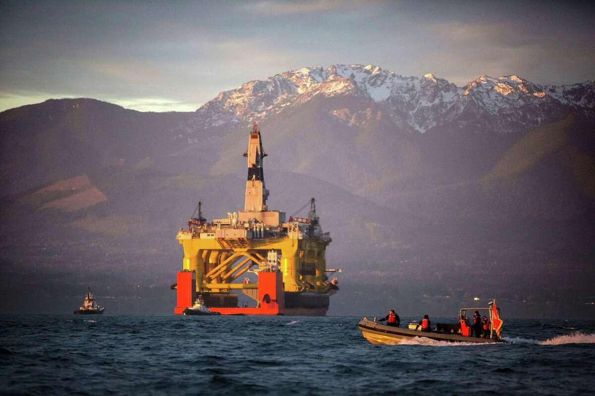 In this April 17, 2015 file photo, a small boat crosses in front of the Transocean Polar Pioneer, a semi-submersible drilling unit that Royal Dutch Shell leases from Transocean Ltd., as it arrives in Port Angeles, Wash. aboard a transport ship after traveling across the Pacific before its eventual Arctic destination. The Interior Department announced Friday, Oct. 16, it is canceling future lease sales and will not extended current leases in Arctic waters off Alaska's northern coast, a decision that significantly reduces the chances for future Arctic offshore drilling. (Daniella Beccaria/seattlepi.com via AP, File) MAGS OUT; NO SALES; SEATTLE TIMES OUT; TV OUT; MANDATORY CREDIT