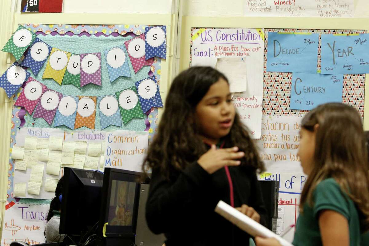 Third-graders Audrey Samora (left) and Olivia Garcia go over a lesson at SAISD's Bonham Academy in Southtown.
