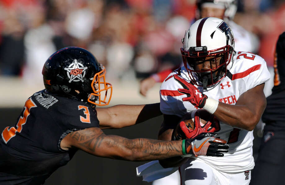 Oklahoma State safety K. Edison McGruder (3) reaches for Texas Tech running back Demarcus Felton (27) during the first half of an NCAA college football game in Stillwater, Okla., Saturday, Nov. 12, 2016. (AP Photo/Brody Schmidt)