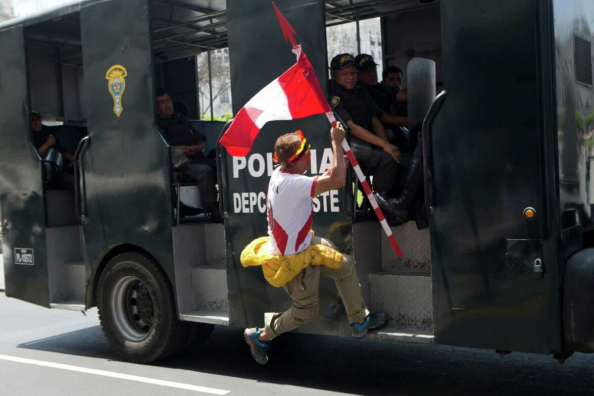 """A man jumps onto a police vehicle during a rally of indigenous people protesting against the pollution resulting from oil production in the Amazons region in Lima, Peru, Friday, Nov. 18, 2016. A small group of anti-globalization activists shouting """"Get Out Obama"""" and """"TPP kills"""" have been protesting near the convention center where an Asia-Pacific Economic summit is taking place. Obama is expected to arrive in the Peruvian capital Friday to attend the summit. (AP Photo/Esteban Felix)"""