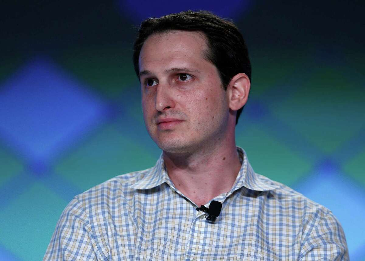 FILe - In this Sept. 29, 2015, file photo, Jason Robins, center, CEO of DraftKings website, speaks on a panel at the Global Gaming Expo in Las Vegas. Daily fantasy sports rivals DraftKings and FanDuel have agreed to merge after months of speculation and increasing regulatory scrutiny. The two companies made the announcement Friday, Nov. 18, 2016, saying the combined organization would be able to reduce costs as they work to become profitable and battle with regulators across the country to remain legal. (AP Photo/John Locher, File)