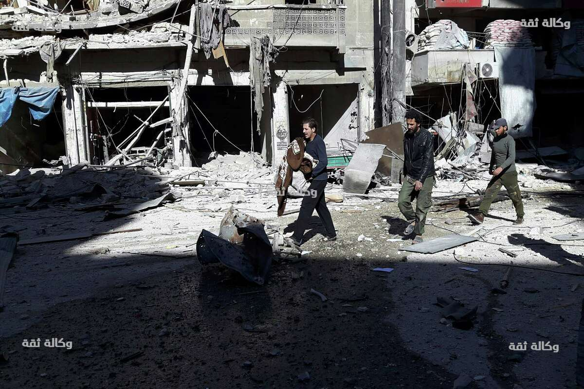 This image released by Thiqa News Agency shows citizens inspecting damaged buildings after airstrikes hit the Al-Shaar neighborhood of Aleppo, Syria, Friday, Nov. 18, 2016. Intensive bombings pummeled Syria's rebel-held eastern neighborhoods of the city of Aleppo on Friday, residents and rescuers said, hitting an area housing several hospitals and sending the chief of a pediatrics clinic in a frantic search for a place to move his young patients. (Thiqa News via AP)