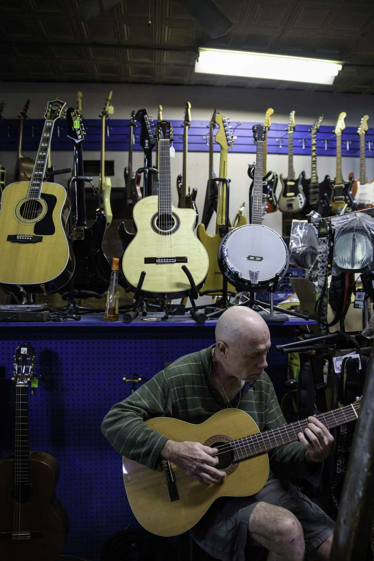 Alex Hussey, a regular customer, strums a guitar amid the vast selection at the Music Guild in Danbury.
