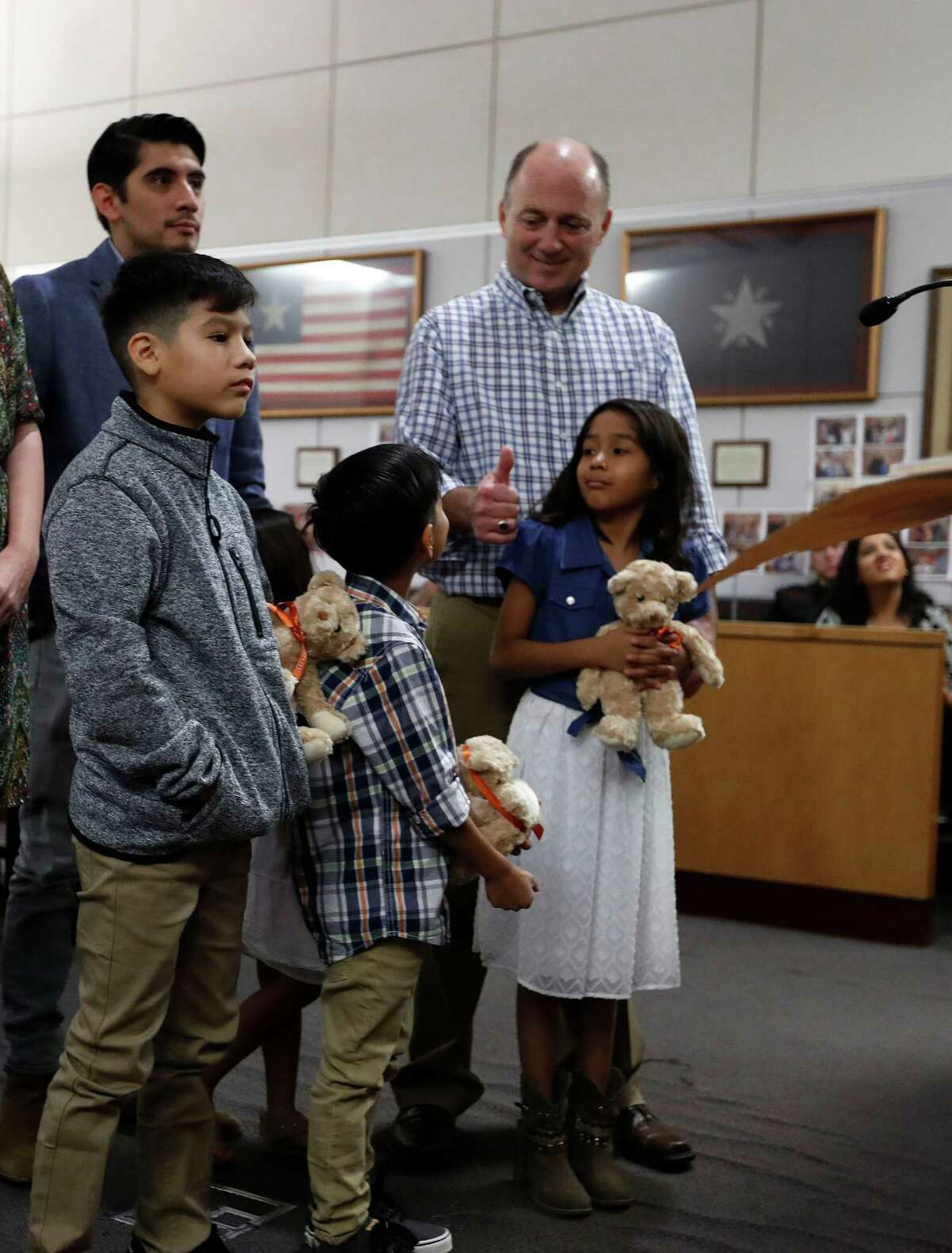 Jeff Aucoin gives a thumbs-up to his newly adopted children: Jason, 8; Ashleigh, 10, and Joshua, 11.