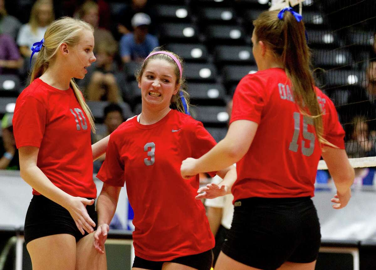 Oak Ridge's Shae Green (3) reacts as Hannah Mikelonis (10) and Hailey Lohnes (15) comfort her after missing a kill shot in the first set of a Class 6A state semifinal match during the UIL State Volleyball Championships at the Curtis Culwell Center Friday, Nov. 18, 2016, in Garland.