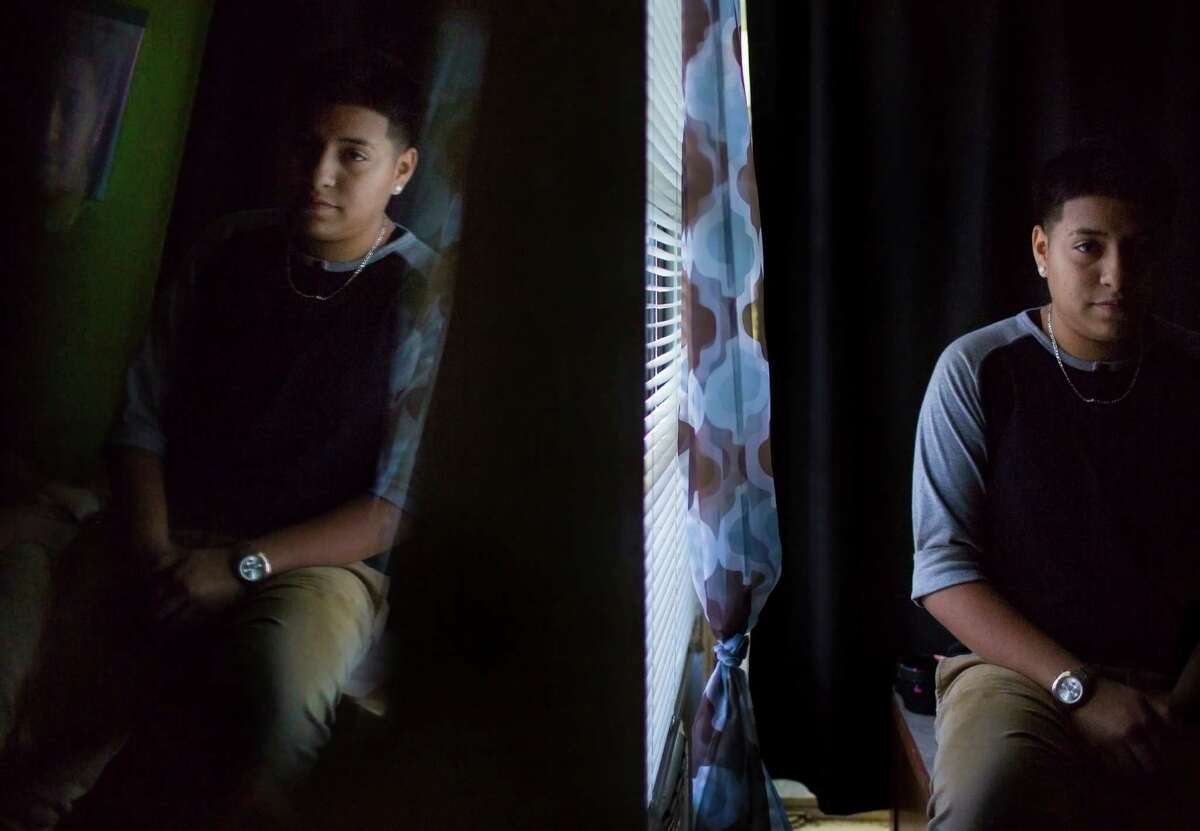 Jacell Rodriguez, 15, is reflected on a glass in her bedroom in San Antonio. Rodriguez suffers from mental illness which is limiting her performance at school.
