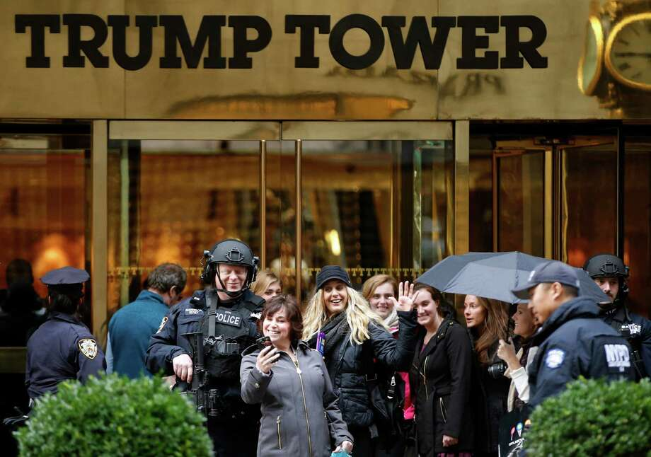 FILE - In this Nov. 15, 2016 file photo, a passersby stops for a selfie with a heavily-armed New York City police officer at the main, Fifth Avenue entrance to Trump Tower in New York. Outside Donald Trump's gilded skyscraper, many in the slow-moving sidewalk throng come for the sole purpose of snapping selfies, some to capture a bit of history and others to offer the new president their one-fingered salute. (AP Photo/Kathy Willens, File) ORG XMIT: NYR401 Photo: Kathy Willens / Copyright 2016 The Associated Press. All rights reserved.