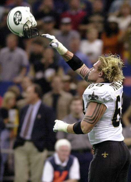 "Saints lineman Turley tosses a Jets helmet during a 2001 game, a move that got him ejected. ""I was a raging maniac,"" he recalls. Photo: CHUCK COOK, AP"