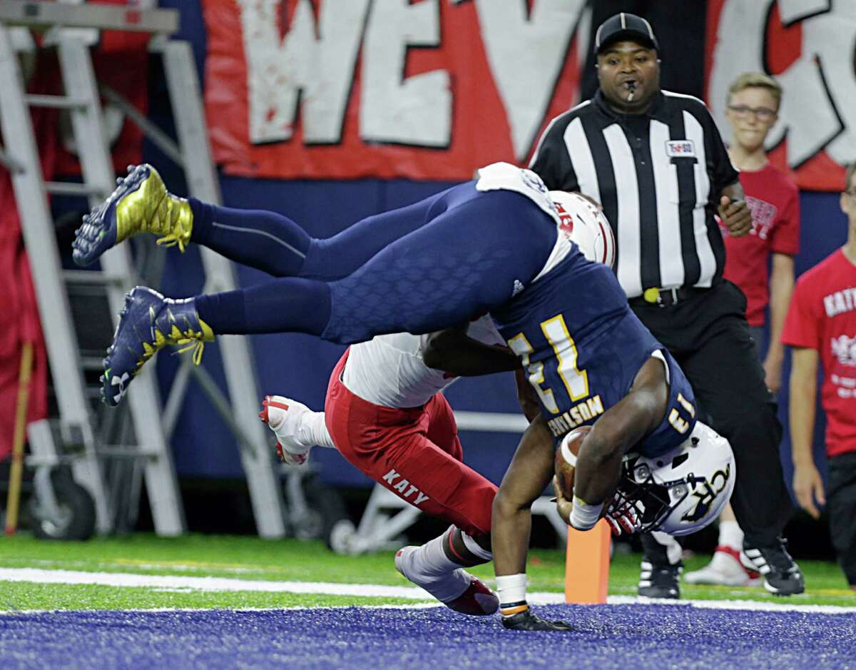 Cypress Ranch's Austin Goffney right, tumbles past Katy's KeShon Rowe left, for a touchdown during second half of Class 6A Division Area playoffs at NRG Stadium Nov. 18, 2016, in Houston.