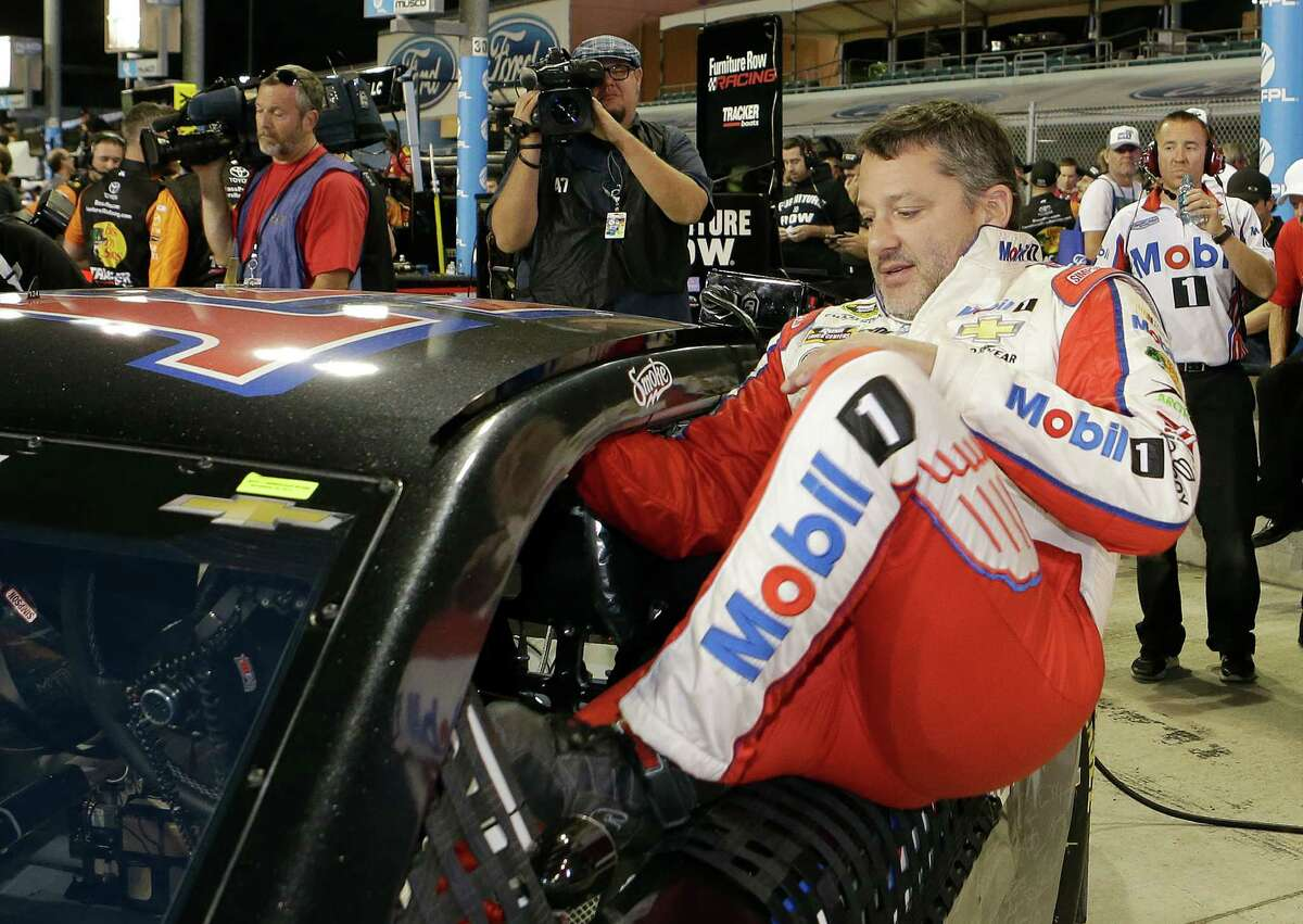 Tony Stewart slips into the cockpit of his car before Friday's qualifying session for the Sprint Cup finale at Homestead, Fla. Stewart qualified 11th in the final race of his NASCAR career.