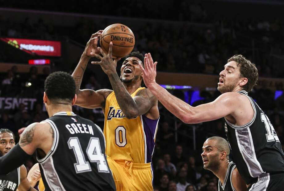 Los Angeles Lakers guard Nick Young, center, goes up against San Antonio Spurs center Pau Gasol, right, and guard Danny Green during the first half of an NBA basketball game Friday, Nov. 18, 2016, in Los Angeles. (AP Photo/Ringo H.W. Chiu) Photo: Ringo H.W. Chiu/Associated Press