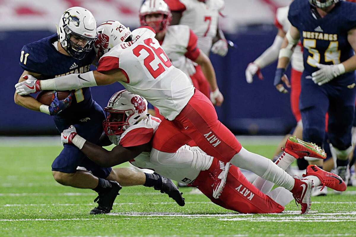 Cypress Ranch's Mason Garner, left, is tackled by Katy's Raymond Randle and Felipe Alvear, right, during first-half action in the battle between Class 6A Division I Region III powers at NRG Stadium on Friday. Katy's defense held the Mustangs to 212 yards.