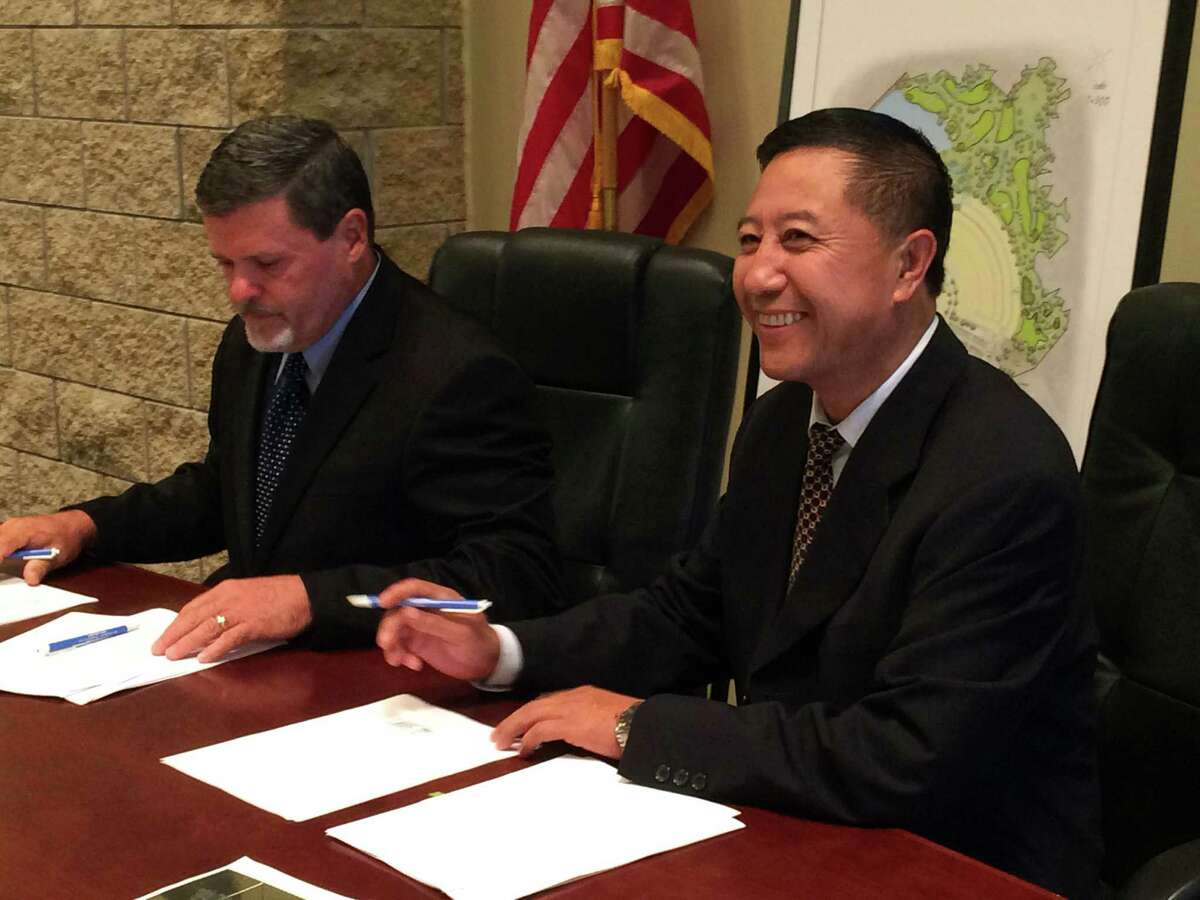 Mayor Niki Coats (left) and Jack Gong of McKinley Develop-ment sign an agreement for an industrial park.
